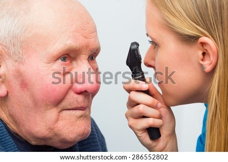 Optician consulting elderly patient with cataracts and other eye problems. - stock photo