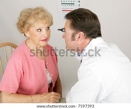 Optician looking into a senior woman's eyes during a routine eye exam. - stock photo