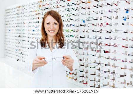 Optician presenting  eyewear frames - stock photo
