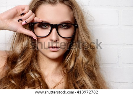 Optics style. Beautiful sexy girl with long wavy hair wearing glasses. Fashion shot.