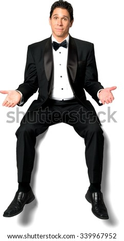Optimistic Caucasian man with short black hair in a tuxedo sitting and pointing using palm - Isolated - stock photo