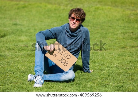 "Optimistic man looking for a job opportunity, holding ""need a job"" cardboard - stock photo"
