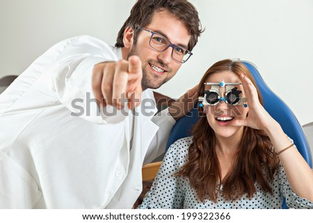 Optometrist Giving Young Woman An Eye Examination - stock photo
