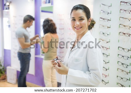 Optometrist looking at the view in glasses store and couple in the background choosing lenses - stock photo