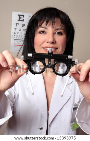 Optometrist or eye doctor about to put trial frames on a patient during a vision checkup. - stock photo