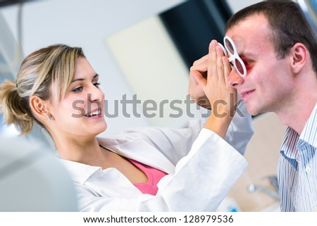 Optometry concept - handsome young man having his eyes examined by an eye doctor - stock photo