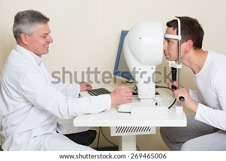 Optometry concept - man having his eyes examined by an eye  elderly doctor. Topography of the cornea. - stock photo