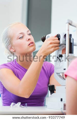 optometry concept - portrait of a young pretty optometrist using slit lamp, checking her patient's sight (color toned image) - stock photo