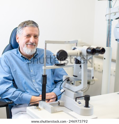 Optometry concept - Senior patient sitting the exmanination chair , before having his eyes examined by an eye doctor, smiling, looking happy - stock photo