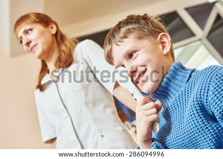 Optometry. female doctor ophthalmologist or optometrist helps to read child boy woman during sight testing or eye examinations in clinic - stock photo