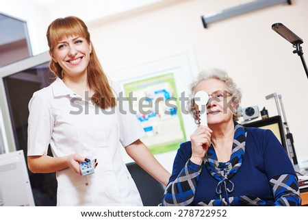 Optometry. female doctor ophthalmologist or optometrist helps to read senior woman during sight testing or eye examinations in clinic - stock photo