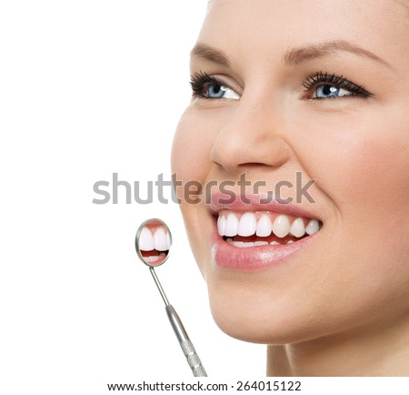 Oral checkup at dentist. Portrait of happy young Caucasian woman with mirror showing her perfect healthy teeth.  - stock photo