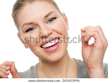 Oral hygiene. Caries prevention. Close-up portrait of young girl using dental floss, isolated over white background.  - stock photo