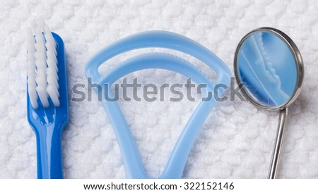Oral hygiene health concept. Closeup dental tools blue toothbrush mirror and tongue cleaner on white towel - stock photo