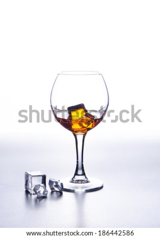 Orange alcohol cocktail in glass with ice cubes on light background, selective focus - stock photo