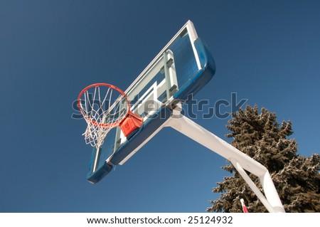 Orange and blue basketball net under bright sky - stock photo