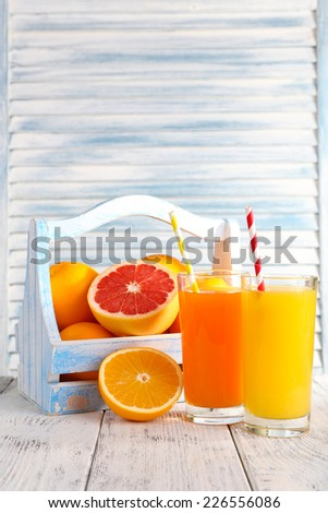 Orange and carrot juice in glasses and fresh fruits in wooden box on wooden table on wooden wall background - stock photo