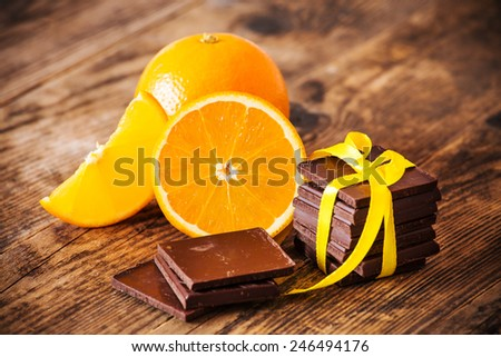Orange and chocolate on the wood table. - stock photo