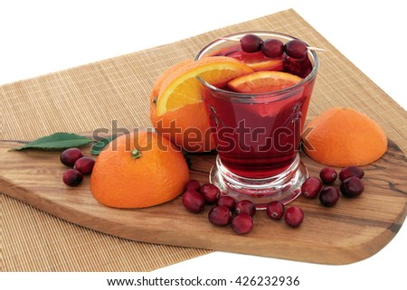 Orange and cranberry juice health drink with fresh fruit on maple wood board and bamboo mat over white background. High in vitamins, anthocyanins, and antioxidants. - stock photo
