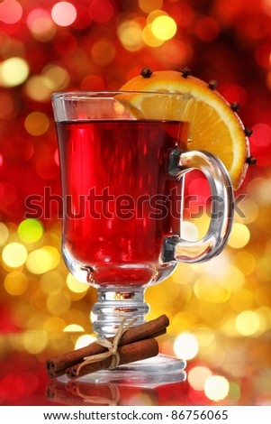 Orange and cranberry punch with spices over Christmas decoration - stock photo