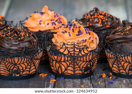 Orange and dark chocolate Halloween cupcakes against rustic background, shallow depth of field - stock photo