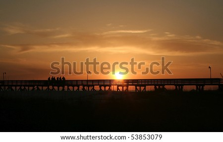 Orange and gold sunset with silhouette of people, pier, and beach. - stock photo