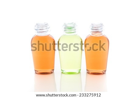 Orange and green bottle of shampoo, gel, soap on a white background with reflection - stock photo