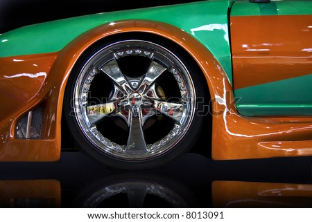 orange and green tuning car, isolated over black mirror - stock photo