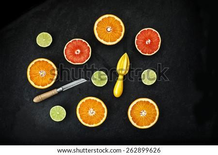 orange and lemon cut on black stone - stock photo