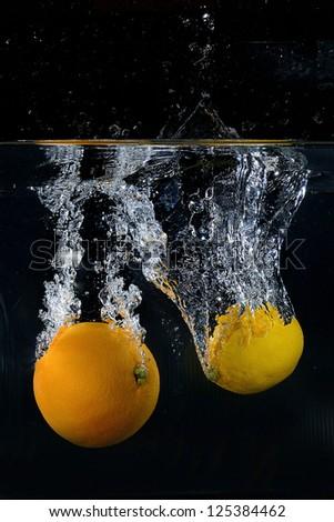 Orange and lemon splash on black background - stock photo