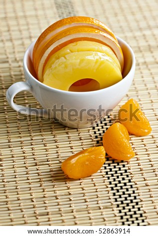 Orange and Pineapple Slices in White Teacup on Placemat - stock photo