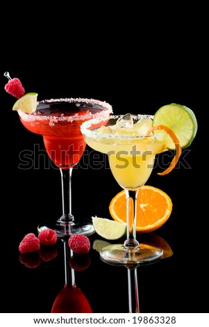 Orange and Raspberry margaritas in chilled glass over black background on reflection surface, garnished slice of fresh lime, orange, and raspberries. Most popular cocktails series.