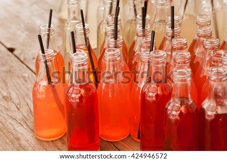 Orange and red color refreshing drinks inside the small bottles with tubes on a wooden table in a outdoor cafe. Still-life with energy cocktails - stock photo