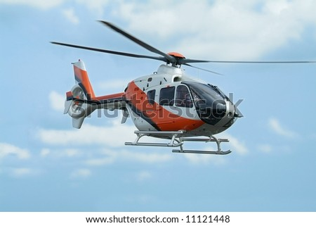 Orange and silver coloured helicopter flying above - stock photo
