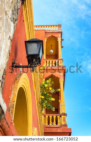 Orange and yellow balconies in the neighborhood of Getsemani in the historic city of Cartagena, Colombia - stock photo