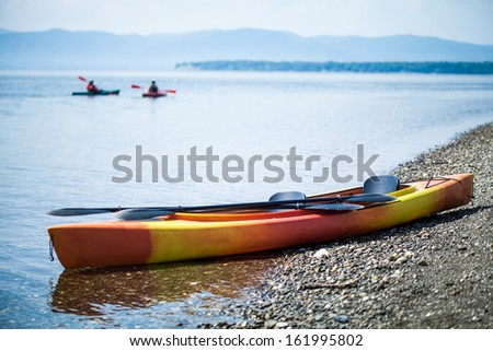 Orange and Yellow Kayak on the Sea Shore During a beautiful Day of Summer with Unrecognizable People Kayaking in the Background - stock photo