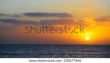 Orange and yellow sunset over the sea - stock photo