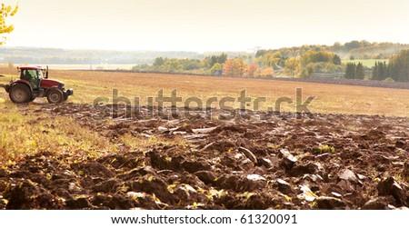 orange autumn field with agrimotor - stock photo