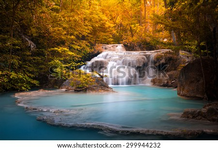 Orange autumn leaves of wild dense forest and scenic waterfall falls in natural blue water pond - stock photo