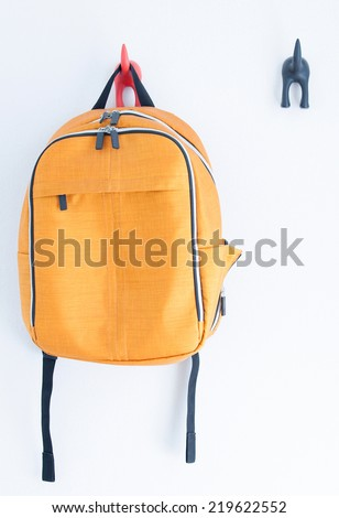 Orange backpack on the wall - stock photo