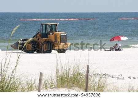 ORANGE BEACH, AL - JUNE 10: A lone beachgoer sits under an umbrella on June 10, 2010 as oil spill workers try to clean up the oil washing ashore at Perdido Pass, AL. - stock photo