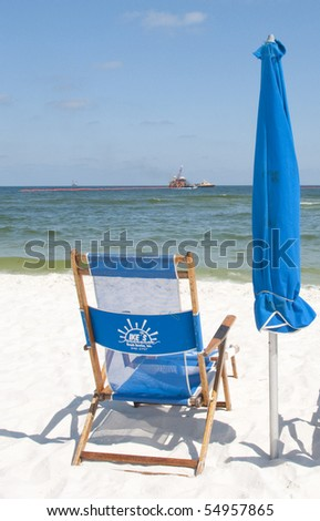 ORANGE BEACH, AL - JUNE 10: Empty beach chair on June 10, 2010 at the height of tourist season at Perdido Pass, AL as the tourism industry suffers from the oil spill (clean up efforts in background). - stock photo