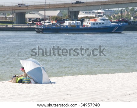 ORANGE BEACH, AL - JUNE 10:  Lone beach goer sits on beach of Perdido Pass, AL on June 10, 2010 as an oil spill boat cruises past BP oil spill staging area in distance. - stock photo