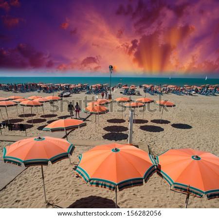 Orange beach umbrellas near the sea at sunset. - stock photo