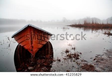 Orange boat in beautiful morning misty light - stock photo