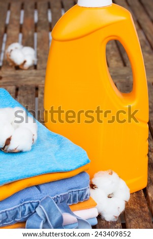 orange bottle of detergent and cotton clothes on wooden table - stock photo