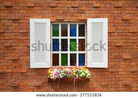 orange brick wall and white wood window with colorful flowers - stock photo