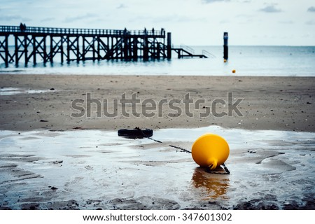 Orange buoy on a beach, pier in the background in Noirmoutier, France. Film emulation filter applied. - stock photo