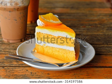 Orange cake and cold coco on wooden background - stock photo