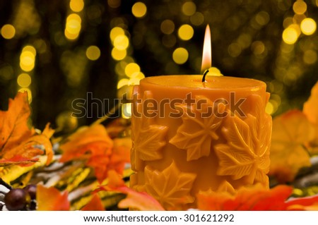 Orange candle in autumn Christmas setting in front of a golden background - stock photo